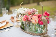 Beautiful Centerpiece created with individual vases on a mirrored tray. Love this! Great idea from Amy Atlas!!