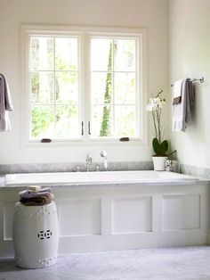 A Nod to Simplicity  This bathtub is a fusion of unrivaled style and understated simplicity. Inconspicuous linen-white walls serve as the backdrop for a sliver of gray stone that wraps around the tub surround. Although small, the detailed faucet and handheld shower fall in line with the simple yet elegant credo of the space.
