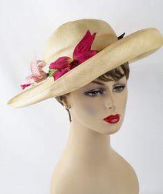 Beautiful flexible natural straw wide brim hat.  Crinkle crown wrapped with 3 mauve irises on green stems.  Asymmetrical brim turns up on one side and