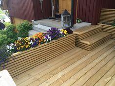 Uteplass og blomsterkasser av impregnert treverk. Blomsterkasse med treverk lagt horisontalt og matchende trapp fra uteplass.
