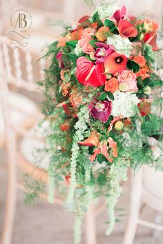 Bridal waterfall bouquet in stunning reds and oranges surrounded with the softest of greens.  Anthurium's, calla lillies, bold white hydrangeas are set off by trailing amaranthus in the palest of greens.