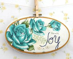 Pretty print fabric, framed in an embroidery hoop, then a word is embroidered on it. I can do this!
