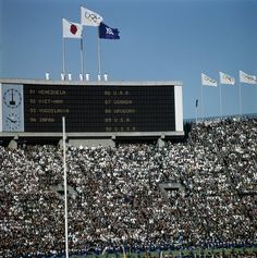 The 1964 Tokyo Olympic Opening Ceremony TOKYO, JAPAN - OCTOBER 10: The Olympic fflag flies over the scoreboard showing the list of the parade of Nations during the opening ceremonies for the XVIII Olympiad at the Olympic Stadium on October 10, 1964 in Tokyo, Japan. (Photo by Michael Ochs Archive/Getty Images) *** Local Caption ***