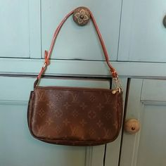 Louis Vuitton Monogram Pochette Handbag Authentic Louis Vuitton handbag. It is the Monogram Pochette style. The serial number is AR0997. Very clean in the inside. Handle leather is pealing apart. Still very easy to wear. A great staple for your closet. Louis Vuitton Bags Shoulder Bags
