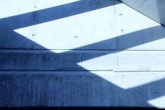 Fotografie van vlakken: Een combinatie van een donkergrijs vlak en verschillende lichtgrijze vlakken die ontstaan zijn door schaduw.