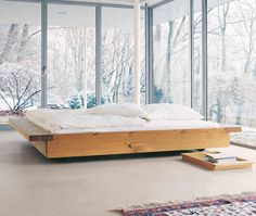 """Designed Philippe AllaeysThe Noah bed is an impressive structure in solid oak, which is especially compelling due to the extended frame on both sides that can also act as a shelf. The floating character of the Noah bed stands as an interesting contrast to the solid wood material. The bed frame is 2 3/8"""" thick and made of four parts, whereby the two boards at the ends are firmly connected in place. The solid wood bed rests on runners with adjustable feet and floats 2 3/8"""" high. The mattress…"""