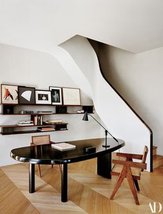 A stair twists into the living room. Charlotte Perriand table and bookshelf; Pierre Jeanneret armchairs; desk lamp from Wyeth.