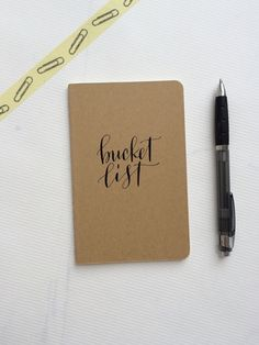 ocketsize Moleskine    This cover is handlettered in a modern script style, using black pigmented calligraphy ink and reads : bucket list