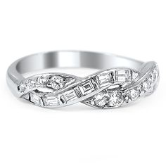 Both timeless and distinctive, this beautiful Retro-era ring features interwoven ribbons of platinum, one featuring diamond baguettes and one holding channel set round diamonds