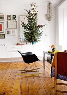 eclectic christmas vignette.  Love the eames rocker, gallery wall, crystal chandelier, and potted pine tree.