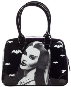 Beautiful purse from Rock Rebel features the infamous Countess of Shroudshire batting her mesmerizing eyes! With it's roomy fully lined interior, side pockets, double straps and silver hardware, this black and purple vinyl purse,  polyester lining zipper closure 11 in. wide, 8 in. tall, 5 in....