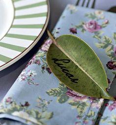 Um idéia simples e bonita para marcar o lugar de seus convidados é escrever os nomes em folhas.