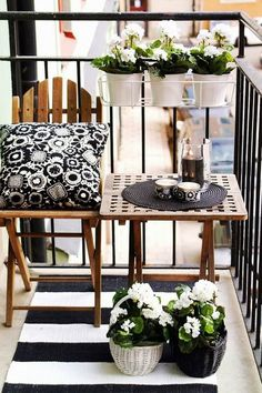 Small balcony decor idea: 1) Use wood furniture mixed with black and white decor items. 2) Place a rug for comfiness. 3) Use planter hanger from railing and some plants on the floor.