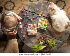 Easter day. Family preparing for Easter. Little cute child painting Easter eggs on wooden background with a cat rabbit bunny.
