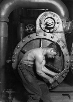 """Lewis Hine photographer Lewis Hine's 1920 Power house mechanic working on steam pump, one of his """"work portraits"""", shows a working class American in an industrial setting. The carefully posed subject, a young man with wrench in hand, is hunched over, surrounded by the machinery that defines his job. But while constrained by the machinery (almost a metal womb), the man is straining against it—muscles taut, with a determined look—in an iconic representation of masculinity."""