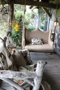 Great idea with the upholstered, cushy swing in a rough hewn covered porch...