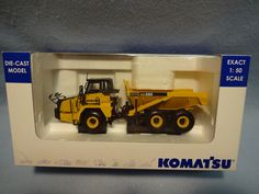 """This Die Cast Model Komat'su HM250 Articulated Dump Truck with three axles and articulating frame is superbly detailed and beautifully finished. It is 1/50 scale, 8"""" long and comes in the like new original box. The truck is like new and has only been removed from box to photograph."""