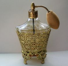 This beautiful glass bottle is encased in a 24KT gold plated ormolu case which stands on four feet. It has a graceful top that also has a gold