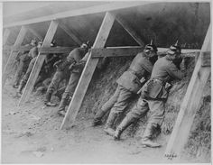 Germans in their well protected trenches on the Belgian frontier showing the men in the act of aiming at their enemy. Underwood and Underwood., 1917 - 1919