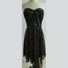 Adrianna Papell Black and gold strapless dress This dress has faux leather lining around the strapless bodice, it is black with gold dots, it is flowy and sheer at the bottom, it's 20 inches long from waist.  100% polyester.  This dress would be perfect as an evening, formal, prom dress! Adrianna Papell Dresses Strapless
