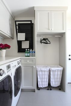 Chic laundry room features light gray cabinets topped with light gray countertops over front-load washer and dryer next to wall-mounted dryer rack as well as built-in rod over laundry sorters.