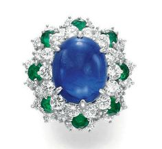 A SAPPHIRE, DIAMOND AND EMERALD RING, BY OSCAR HEYMAN & BROTHERS   Set with an oval cabochon sapphire, within a three-tiered circular-cut diamond and emerald surround, mounted in platinum and 18k gold  By Oscar Heyman & Brothers, no. 68917