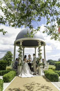 Beautiful open air ceremony decorated with blush, ivory and coral flowers at Froyle Park by Fiona Curry Flowers.