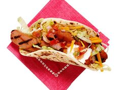 Taco Dogs Wrap grilled halved hot dogs in grilled flour tortillas; top with shredded cheddar, lettuce, salsa and sour cream.
