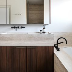 Architecture studio Dieter Vander Velpen has employed a luxurious material palette of dark walnut, black granite and limestone to overhaul the kitchen and bathroom of a house in Belgium.