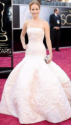 Jennifer Lawrence, 2013  Jennifer Lawrence stole the show in a strapless Dior Haute Couture pale blush gown that she styled with Chopard diamonds and a metallic Roger Vivier clutch. The Best Actress winner for Silver Linings Playbook wore pear-shaped white diamond drop earrings, plus a white diamond band, floral diamond ring, and the show-stopping centerpiece: a 74-carat strand of 150 diamond beads, which she wore backwards, draping down her back.