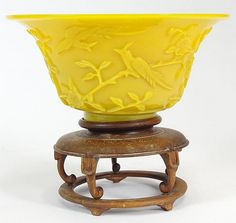 Chinese 19th Century Imperial Yellow Peking Glass Bowl with Carved Bird and Flowering Branch Decoration and Carved wood base. Unsigned. Calcification to Interior otherwise good condition. Measures 3-1/2 Inches Tall and 7 Inches Wide