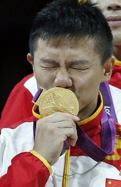 Chinese gymnast Chen Yibing kisses his gold medal after his team won the Artistic Gymnastic men's team final.