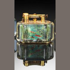 """DUNHILL: An 'Aquarium' lighter,  gilt mounts, Perspex body, engraved and painted, each side depicting three fish in gold, red and silver, on a green ground with water plants and rocks, incuse stamped to underside of base """"Dunhill Lighter"""", """"Made in England"""", height 7.4cm, length 9.5cm, width 5.2cm."""