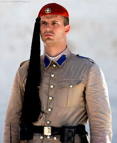 The Evzones - The Evzones, or Evzoni is the name of several historical elite light infantry and mountain units of the Greek Army. Today, it refers to the members of the Presidential Guard, an elite ceremonial unit that guards the Greek Tomb of the Unknown Soldier, the Presidential Mansion and the gate of Evzones camp in Athens. Unknown Soldier, Urban Photography, Athens, Gate, Captain Hat, Army, Mountain, The Unit, Mansions