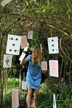 Cards hanging in trees are very affective. You can pick up different sized decks from $2 shops very easy to do and very cute!