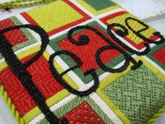 Painted canvas needlepoint by Raymond Crawford, stitch guide by Suzanne Howren and Beth Robertson. Uses Kreinik Facets in black for the lettering.
