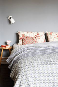 Credit: Rachel Whiting Vintage, mismatched floral bedlinen from British companies such as Liberty and Toast has been mixed together with lin...