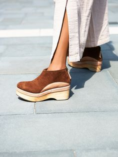 Camilla Suede Clog   Inspired by decades past these suede clogs feature leather trim and a wooden platform. Back zip closure for an easy on-off and a rubber sole.