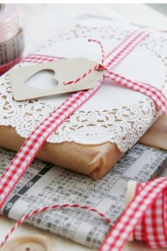 Newspaper wrap, kraft wrap tied together with red ribbon.