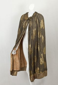 Liberty & Co. gold lamé evening cape, 1920s. By the mid 1920s, fashion taste and Liberty textiles had moved away from the nostalgic images of Art Nouveau to more streamlined Art Deco styles. The dazzling cape features bold Deco-style gold tulips on a textured ground of black and gold. The gold threads have developed a fine burnished patina—the tribute that time pays to beauty.