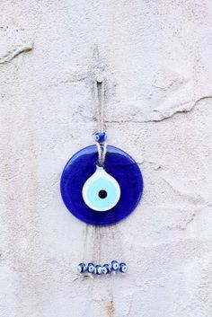"""This single, glass, pericing blue Nazar Boncuk charm is handmade in Turkey and features jute string with dangling beaded accents. More commonly known as the """"evil eye"""", the vibrant glass eye is usually hung in homes, cars or even worn to ward off negative energy and evil spirits. The eye serves as a reminder that we are all one people regardless of religion or ethnicity."""