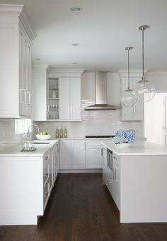 Beautiful kitchen features a pair of clear glass globe pendants illuminating a center island painted light gray fitted with microwave nook topped with honed white marble.