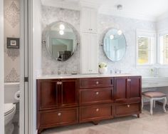 This master bathroom features a cherry vanity that has been elegantly finished with crystal knobs and a Carrara marble countertop. Two oval pivot mirrors are positioned above the vanity, along with a pair of globe pendant lights. Just under the windows is a makeup area, the perfect space for getting ready in natural light.
