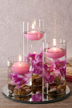 Set Of Three Lilac Floating Candles (£22) Set of 3 decorative glasses filled with lilac pebbles, artificial flowers and floating candles all on a mirrored base. Tallest glass is 20cm. Base diam. 20cm