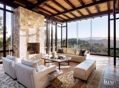 The living area, with window systems built by 4th Street Woodworking, takes advantage of the site's expansive mountain vistas. The fireplace was constructed with stone unearthed from the property. A 19th-century Agra rug anchors a sofa and armchairs by Christian Liaigre and a coffee table by Jean de Merry.