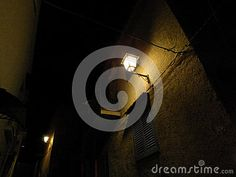 Night lamp posts on ancient wall with wooden window shades