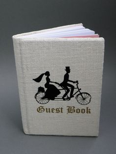 Customized Linen Wedding guest book Black Silhouettes Vintage groom and bride on bicycle. $39.00, via Etsy.