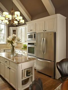 taupe colored kitchen with a breakfast bar low, white wooden furniture