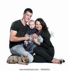 Portrait of young family with baby boy and 2 months old wolf cub in front of white background, studio shot by Eric Isselee, via ShutterStock