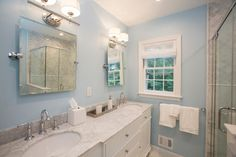 After the renovation, the master bathroom in Tom and Bridget Suvansri's new home is bright and spa-like, with marble floor and shower tile, twin vanities, and plenty of under-sink storage.